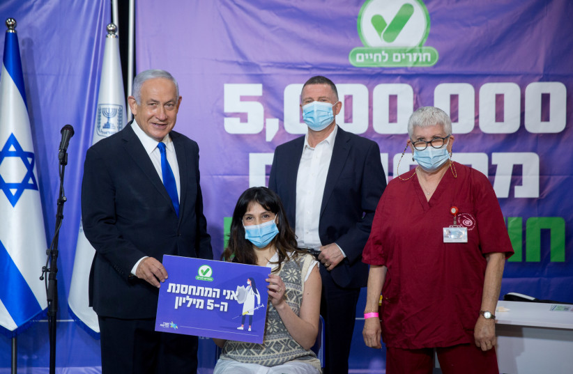 Prime Minister Benjamin Netanyahu and Health Minister Yuli Edelstein pose for a photograph with Janet Lavi-Azulay, 34, the 5 millionth Israeli to get the Pfize vaccine, in Tel Aviv on March 8 (photo credit: MIRIAM ALSTER/POOL/REUTERS)