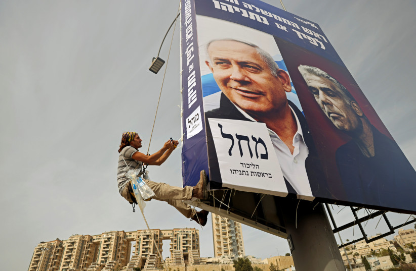 A man hangs a Likud election banner, depicting party leader Prime Minister Benjamin Netanyahu and his top challenger, Yesh Atid leader Yair Lapi (photo credit: RONEN ZVULUN/REUTERS)