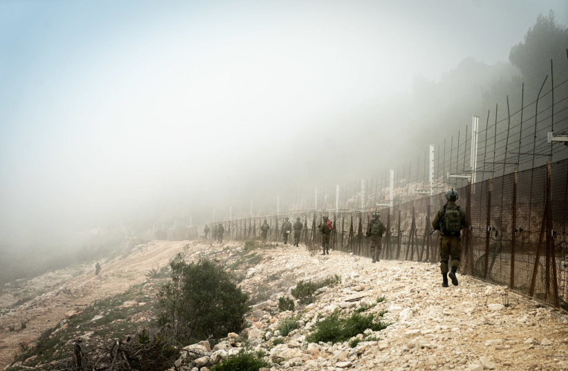 IDF SOLDIERS seen walking in the  enclave, near the fence. (photo credit: IDF SPOKESPERSON'S UNIT)