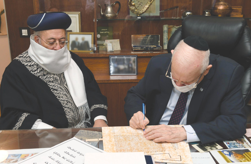 PRESIDENT REUVEN RIVLIN greets  and signs a document appointing Sephardi Chief Rabbi of Jerusalem Shlomo Moshe Ameras his agent in the sale of leave (photo credit: MARK NEYMAN/GPO)