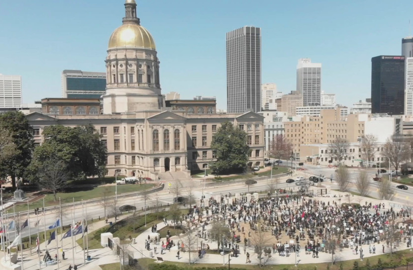 People participate in a Stop Asian Hate rally at Liberty Plaza, next to the Georgia State Capitol, in Atlanta, Georgia, March 20, 2021, in this still image from drone video obtained via social media. (photo credit: ARRHYTHMIA FILMS VIA REUTERS)