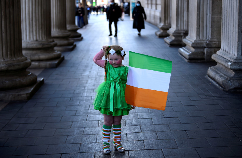 Willow O'Brien, 5, looks at her mother (not pictured) as she holds an Irish flag while posing for pictures, amid the outbreak of the coronavirus disease (COVID-19), on Saint Patrick's Day in Dublin, Ireland, March 17, 2021. (photo credit: CLODAGH KILCOYNE/REUTERS)