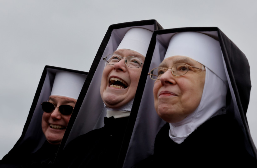 Nuns react as US President Donald Trump holds a campaign rally at Oakland County International Airport in Waterford Township, Michigan, U.S., October 30, 2020.  (photo credit: CARLOS BARRIA / REUTERS)