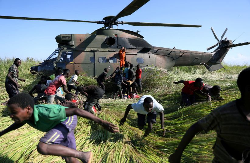People run after collecting food aid from a South African National Defence Force (SANDF) helicopter in the aftermath of Cyclone Idai in Nhamatanda village, near Beira, Mozambique, March 26, 2019.  (photo credit: REUTERS/SIPHIWE SIBEKO)