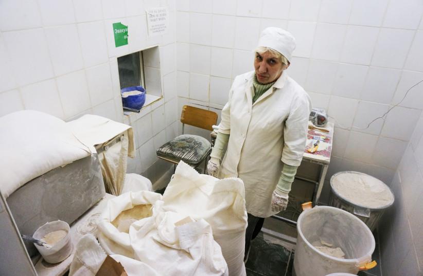 An employee prepares dough at the Tiferet Hamatzot factory in Dnepro, Ukraine, Dec. 8, 2014. (photo credit: CNAAN LIPHSHIZ/JTA)