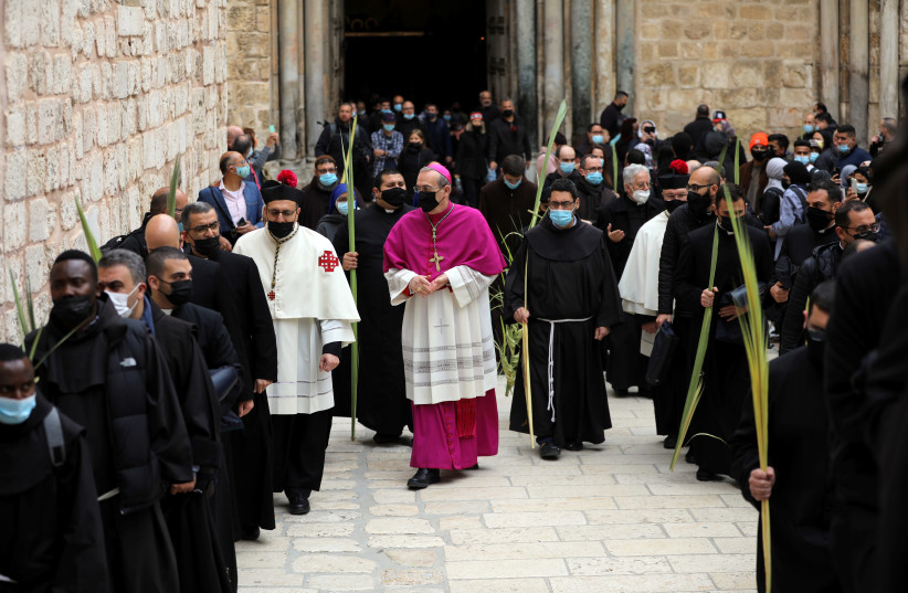 Latin Patriarch of Jerusalem Pierbattista Pizzaballa walks along Christian worshippers and the clergy holding palm fronds during a Palm Sunday procession outside the Church of the Holy Sepulchre in Jerusalem's Old City March 28, 2021. (photo credit: REUTERS/AMMAR AWAD)