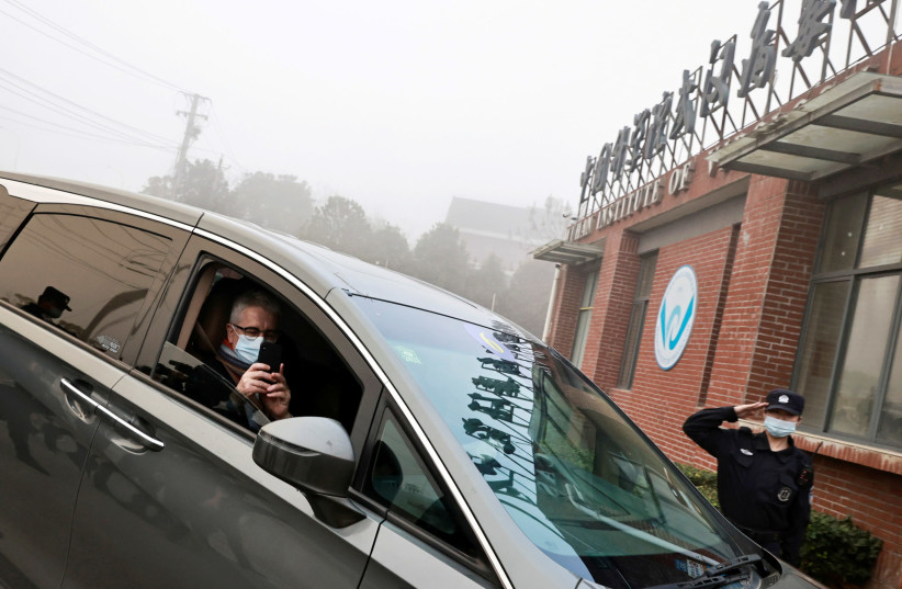 Dominic Dwyer, a member of the World Health Organization (WHO) team tasked with investigating the origins of the coronavirus disease (COVID-19), sits in a car arriving to Wuhan Institute of Virology in Wuhan, Hubei province, China February 3, 2021. (photo credit: REUTERS/THOMAS PETER/FILE PHOTO)