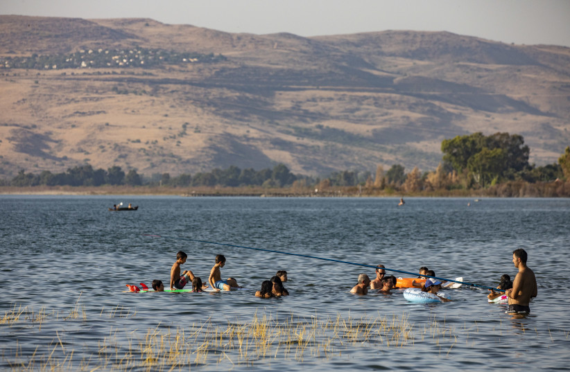 People enjoy and bath in the Sea of Galilee (Kinneret) next to the city of Tiberias on June 23, 2015.   (photo credit: OLIVIER FITOUSSI/FLASH90)