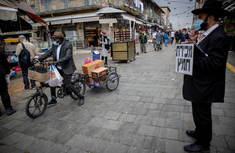 An Ultra orthodox jewish man walks at the Mahane Yehuda market in Jerusalem on March 22, 2021.  (photo credit: YONATAN SINDEL/FLASH 90)