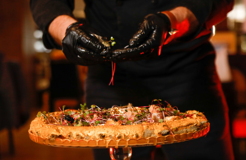 Illustrative Photo: Ahmed Hergal, founder of Italian restaurant L'antica Pizzeria DaPietro, adds ingredients to his 999 DT (360 USD) pizza, covered with luxury foods and edible gold leaf, in Tunis, Tunisia, March 6, 2021. (photo credit: REUTERS/JIHED ABIDELLAOUI)