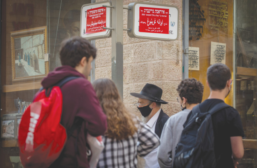 PASSERSBY WALK by signs whose names have been changed to those of women killed in domestic violence in Jerusalem, in November 2020 to mark the Day For Elimination Of Violence Against Women. (photo credit: OLIVIER FITOUSSI/FLASH90)