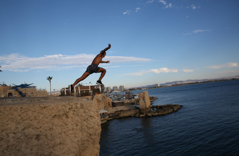A young man jumps in the water in Acre's Old City. (photo credit: DAVID COHEN/FLASH 90)