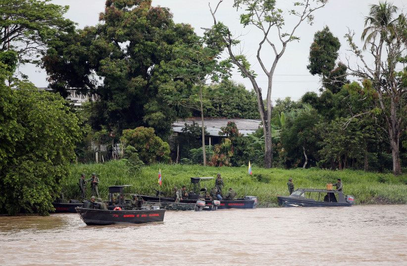 Venezuelan soldiers patrol by boat on the Arauca River, the border between Colombia and Venezuela, as seen from Arauquita, Colombia, March 28, 2021. (photo credit: REUTERS/LUISA GONZALEZ/FILE PHOTO)