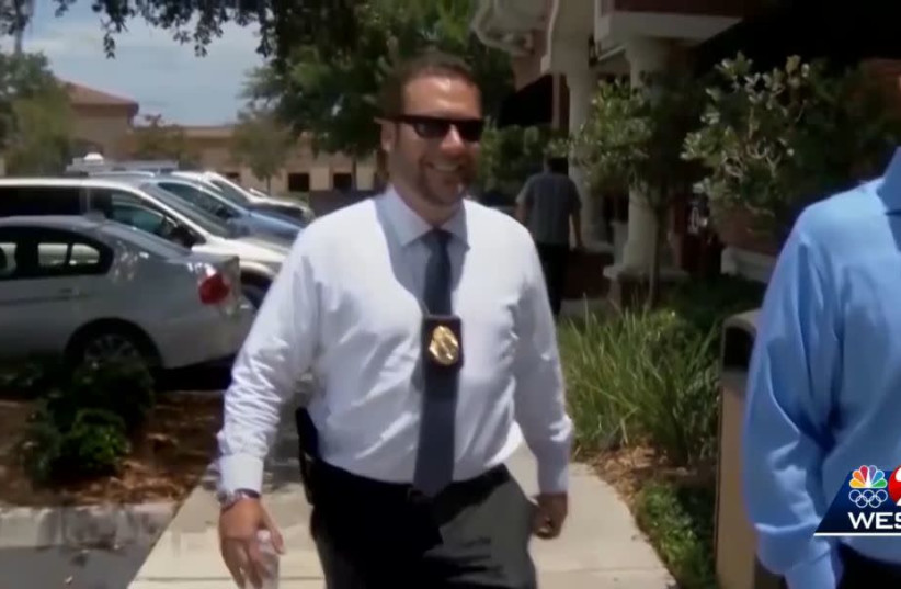 Joel Greenberg, bearing his tax collector badge and a sidearm, appears in a TV news report about his legal troubles in Seminole County, Florida, Jan. 25, 2021 (photo credit: YOUTUBE SCREENSHOT/JTA)