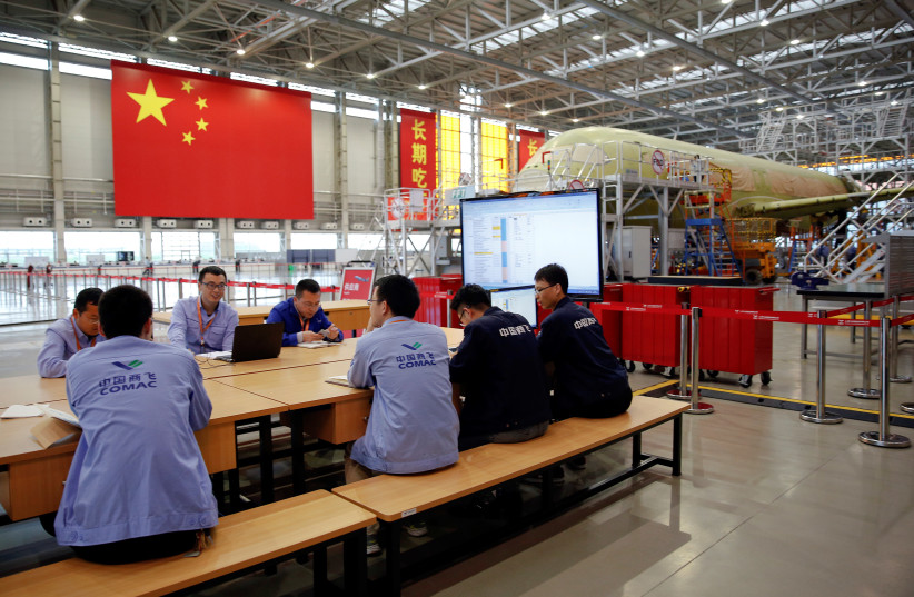 Employees work on a China's home-grown C919 passenger jet at Manufacturing and Final Assembly Center of state-owned Commercial Aircraft Corporation of China (COMAC) during a media tour in Shanghai (photo credit: ALY SONG/REUTERS)