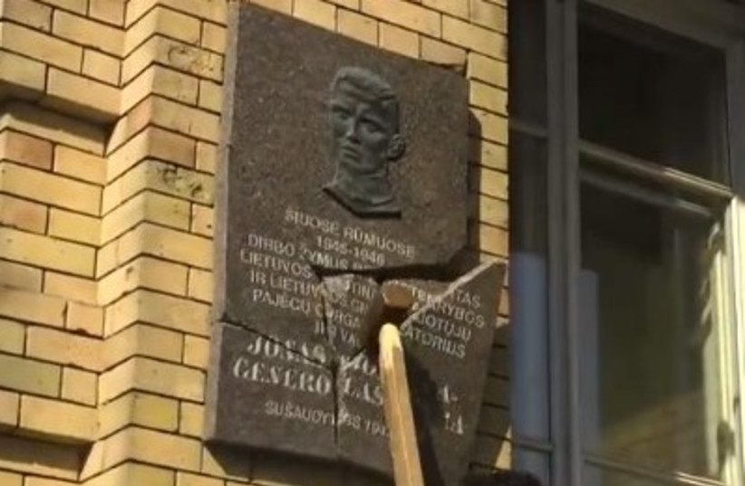 A screenshot of Prof. Dr. Stanislovas Tomas' video in which he destroys a Nazi collaborator's plaque (photo credit: screenshot)