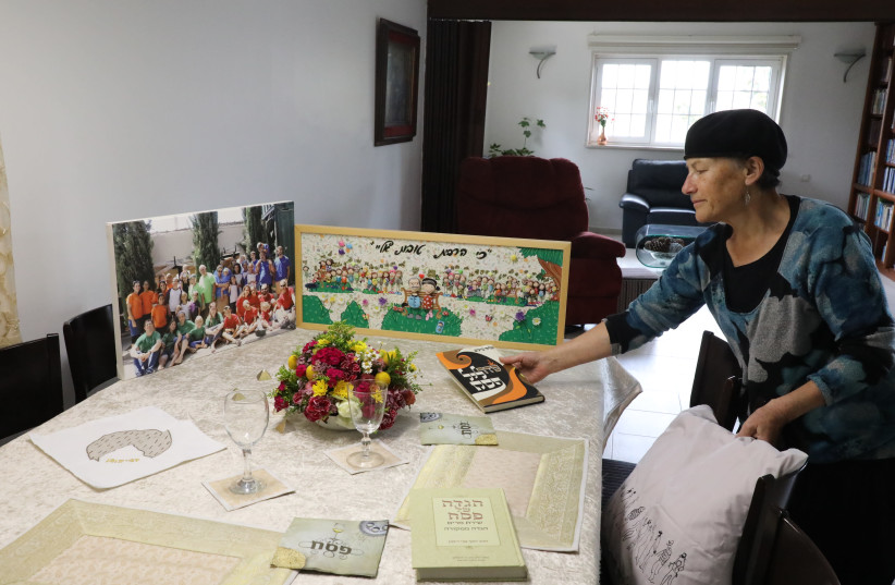 LONELY SEDER: Arranging the 2020 Passover table with pictures of children and grandchildren standing in for the real thing. (photo credit: GERSHON ELINSON/FLASH90)