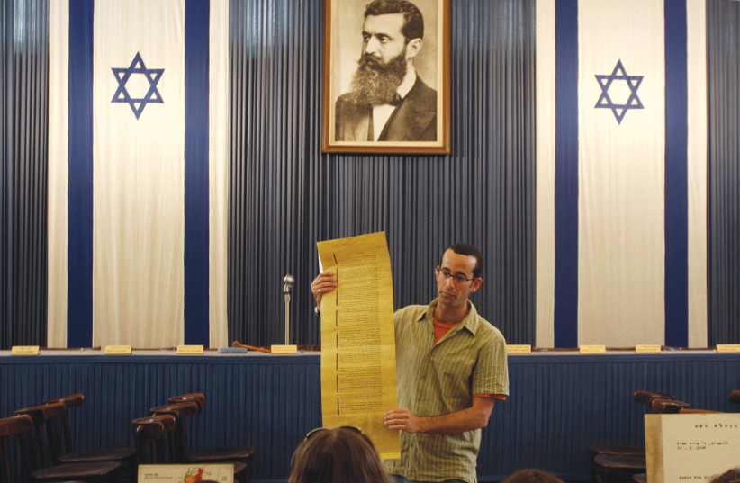 A GUIDE stands under a portrait of Theodor Herzl at Independence Hall in Tel Aviv. Goodman writes about Herzl's hope that Zionism would save the Jews. (photo credit: GIL COHEN MAGEN/REUTERS)