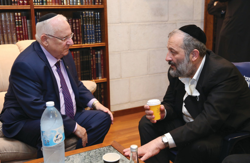 PRESIDENT REUVEN RIVLIN pays a shiva call to Minister Arye Deri upon the loss of his mother, Esther, in Jerusalem in 2017. (photo credit: YAAKOV COHEN/FLASH90)