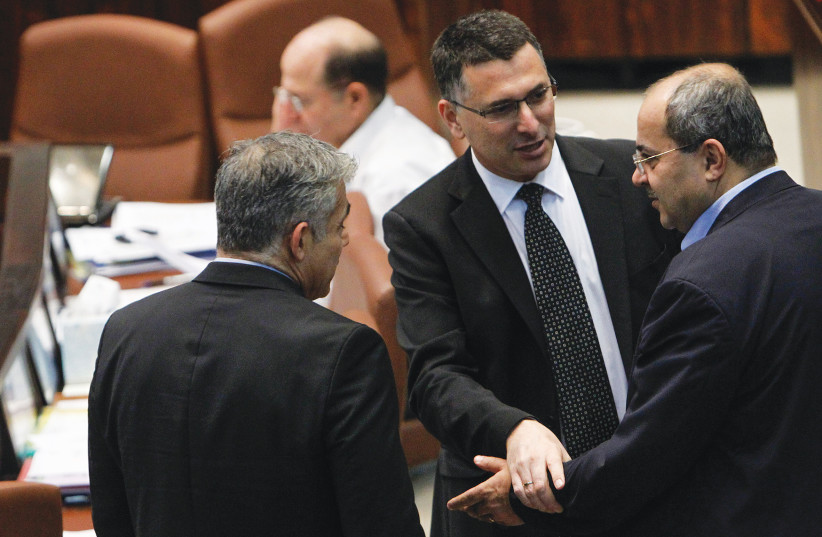 THEN-INTERNAL affairs minister Gideon Sa'ar (center) speaks with Arab parliament member Ahmad Tibi (right) and then-finance minister Yair Lapid during a plenum session in the Knesset in 2013. (photo credit: MIRIAM ALSTER/FLASH90)