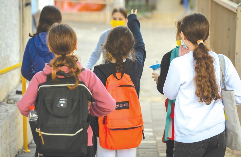 STUDENTS WEARING face masks return to school at Gabrieli Carmel School in Tel Aviv in February. (photo credit: AVSHALOM SASSONI/FLASH90)