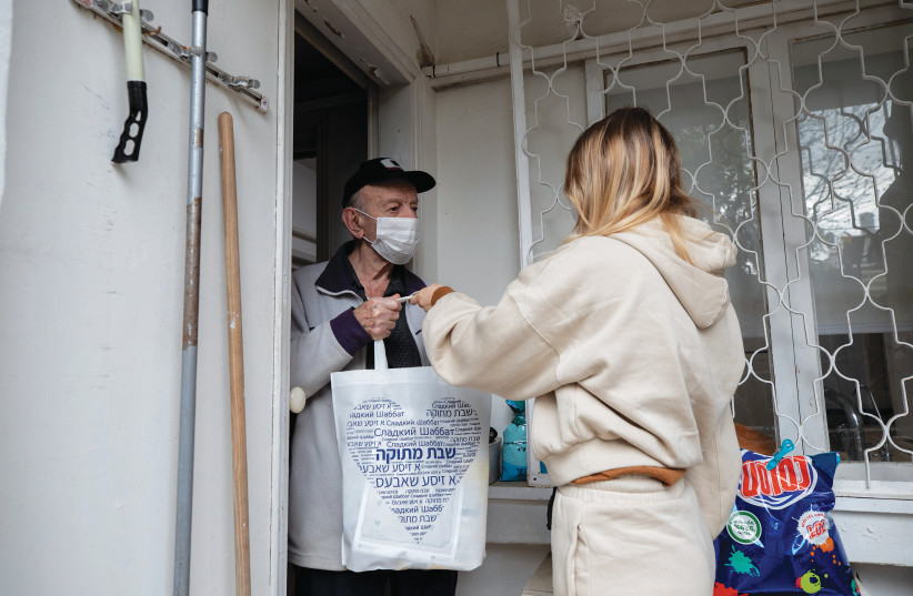 A VOLUNTEER delivers a food package to a Holocaust survivor in Ramat Gan in January. (photo credit: CHEN LEOPOLD/FLASH90)