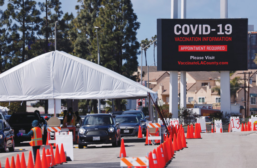 RESIDENTS OF Inglewood, California, receive COVID-19 vaccinations at a temporary vaccine station last month. (photo credit: MIKE BLAKE/ REUTERS)