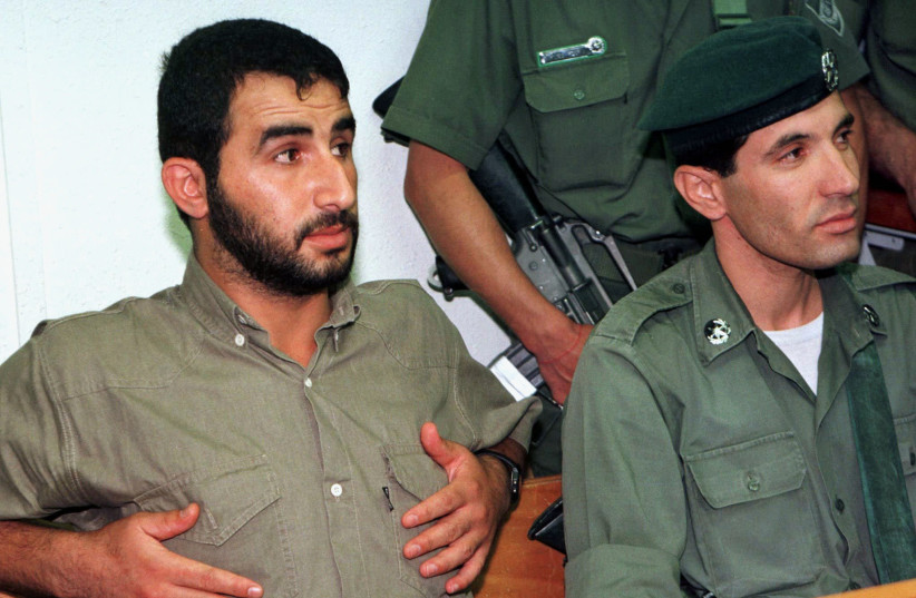 Hassan Salameh, a top member of the Hamas Islamic group, sits back under armed guard on the defendant's bench in an Israeli army military court as he waits to be sentenced July 7. Salameh, convicted of masterminding three Hamas suicide bombings last year which left 45 people dead, was sentenced to 4 (photo credit: REUTERS)