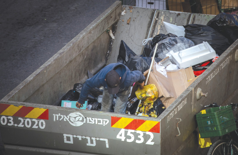 A BOY searches through a garbage container in downtown Jerusalem in December. (photo credit: YONATAN SINDEL/FLASH90)