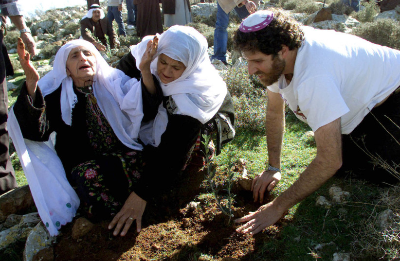 Elderly Palestinian Woman gives thanks as Rabbi Ascherman plants olive trees near Kiryat Arba, 2003. (photo credit: REUTERS)