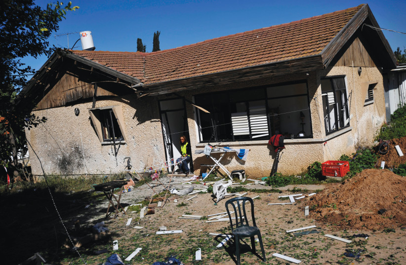 A MUNICIPAL worker sits at the entrance to a damaged house after a rocket fired from Gaza landed in Sderot, February 2009.  (photo credit: AMIR COHEN/REUTERS)