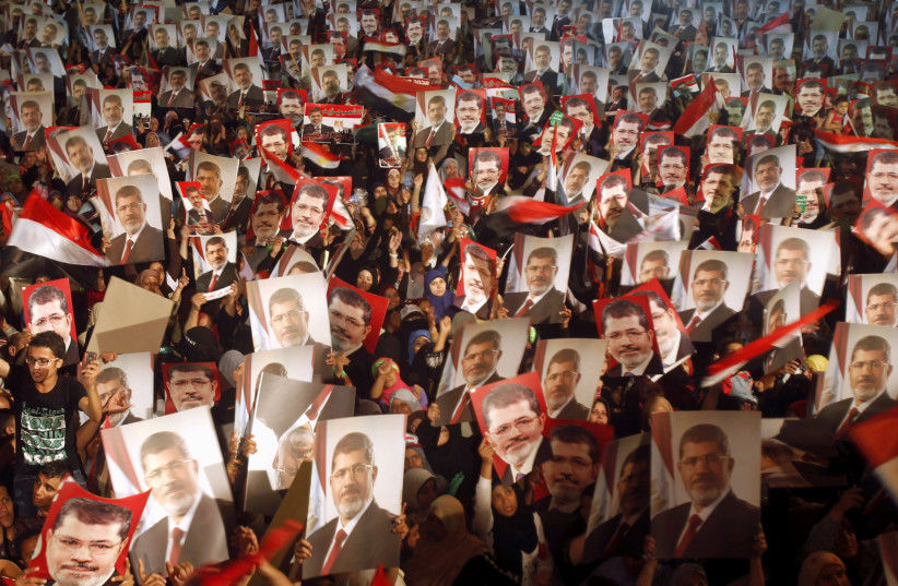 MUSLIM BROTHERHOOD members and supporters of Egyptian president Mohamed Mursi display his photo at Cairo's Raba El-Adwyia mosque square, July 2013.  (photo credit: KHALED ABDULLAH/FILE PHOTO/REUTERS)