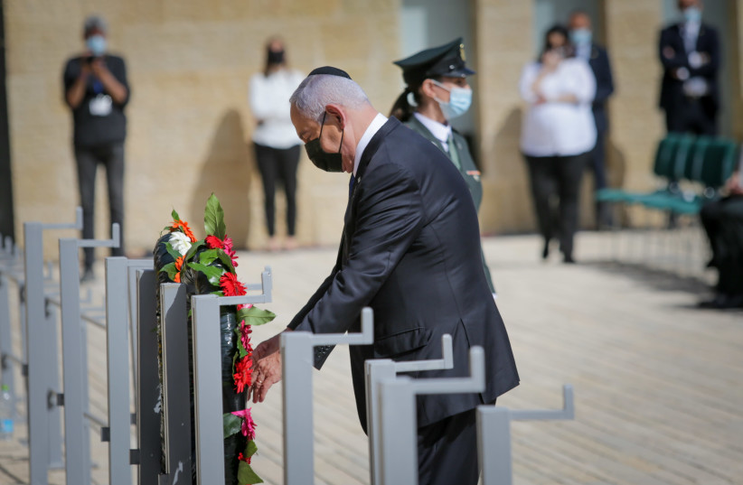 Israeli Prime Minister Benjamin Netanyahu lay a wreath during a ceremony held at the Yad Vashem Holocaust Memorial Museum in Jerusalem, as Israel marks annual Holocaust Remembrance Day. April 8, 2021.  (photo credit: ALEX KOLOMOISKY / POOL)