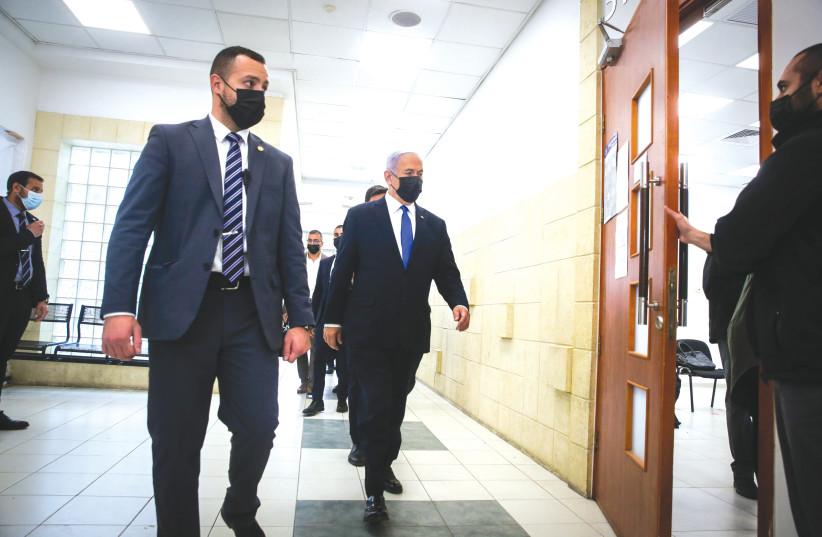 Prime Minister Benjamin Netanyahu makes his way into court on Monday. (photo credit: OREN BEN HAKOON/POOL)
