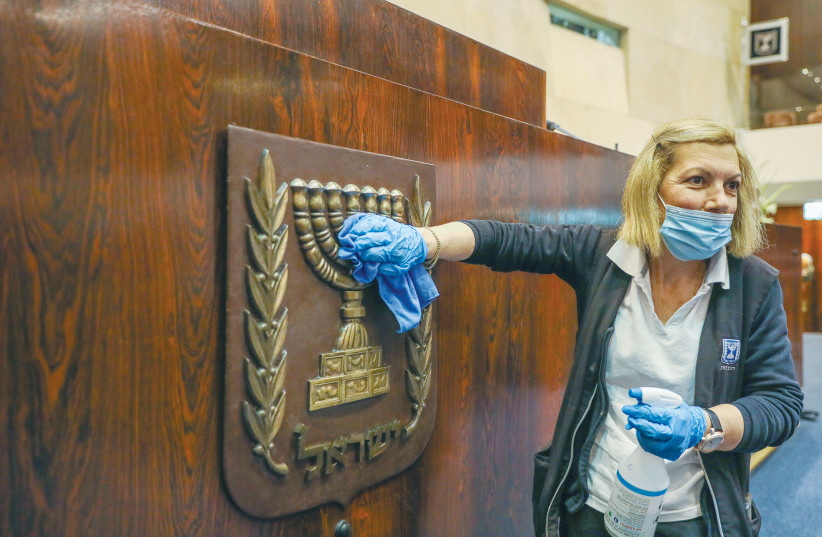 A WOMAN polishes the national symbol at the Knesset ahead of the inauguration ceremony this week. (photo credit: MARC ISRAEL SELLEM/THE JERUSALEM POST)