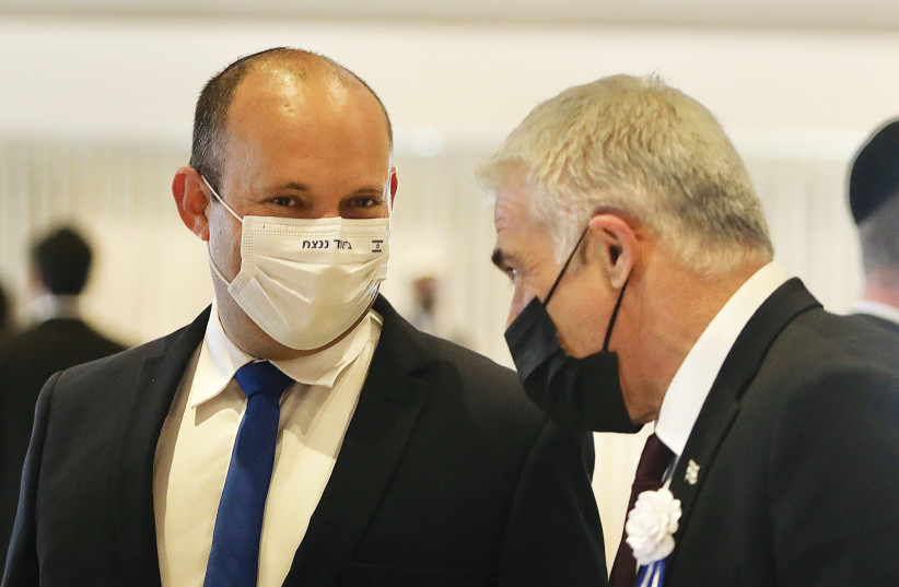 YAMINA LEADER Naftali Bennett (left) talks with Yesh Atid head Yair Lapid at the inauguration of the Knesset on Tuesday. The slogan on Bennett's mask says, 'Together we will win.' (photo credit: MARC ISRAEL SELLEM/THE JERUSALEM POST)