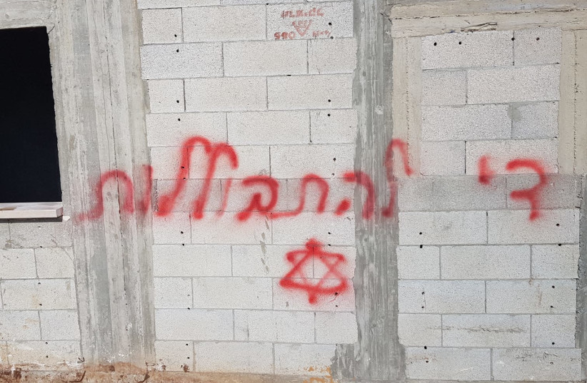 """The tires of over 20 vehicles were punctured early Friday in the Bedouin village of Kamanneh and """"stop assimilation"""" was spray-painted on a wall in the village. (photo credit: ISRAEL POLICE)"""