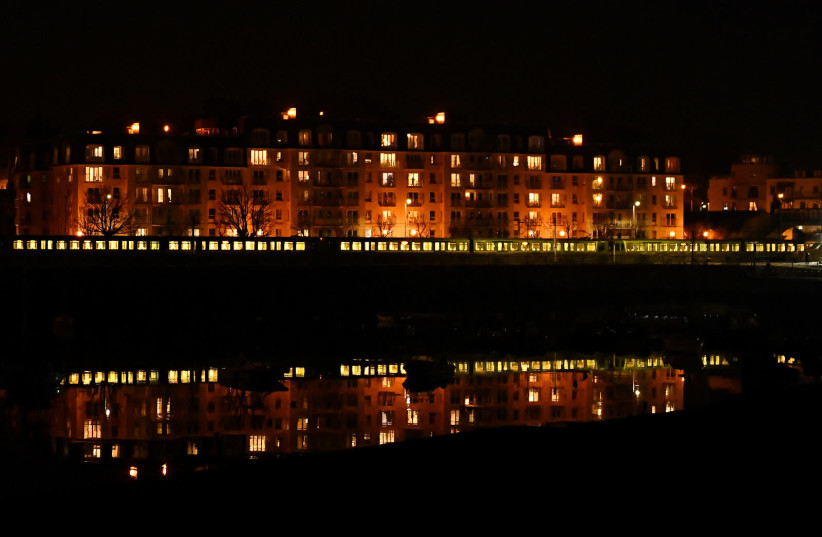 The electric rail DART (Dublin Area Rapid Transit) train is seen reflected in Dun Laoghaire harbour at night, amid the coronavirus disease (COVID-19) pandemic, in Dublin, Ireland, April 3, 2021. (photo credit: CLODAGH KILCOYNE/REUTERS)
