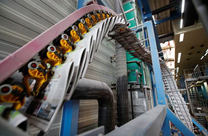 The Journal de Morges newspaper comes out the KBA rotary press at the Centre d'Impression Lausanne in Bussigny (photo credit: DENIS BALIBOUSE/REUTERS)
