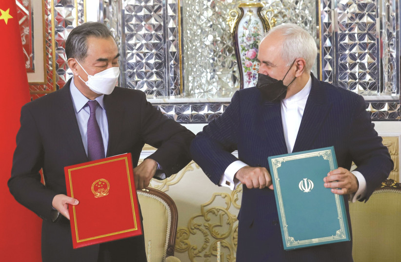 FOREIGN MINISTERS Mohammad Javad Zarif of Iran and Wang Yi of China bump elbows during the signing ceremony of a 25-year cooperation agreement, in Tehran last month. (photo credit: MAJID ASGARIPOUR/WANA/REUTERS)