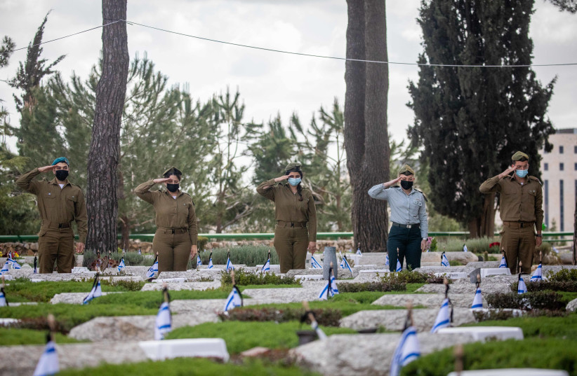 Israeli soldiers place Israeli flags on the graves of fallen soldiers in Mount Herzl Military Cemetery in Jerusalem, on April 11, 2021 (photo credit: YONATAN SINDEL/FLASH90)