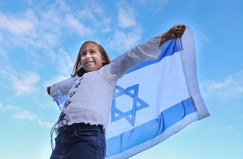 A young girl raises an Israeli flag.  (photo credit: MARC ISRAEL SELLEM)