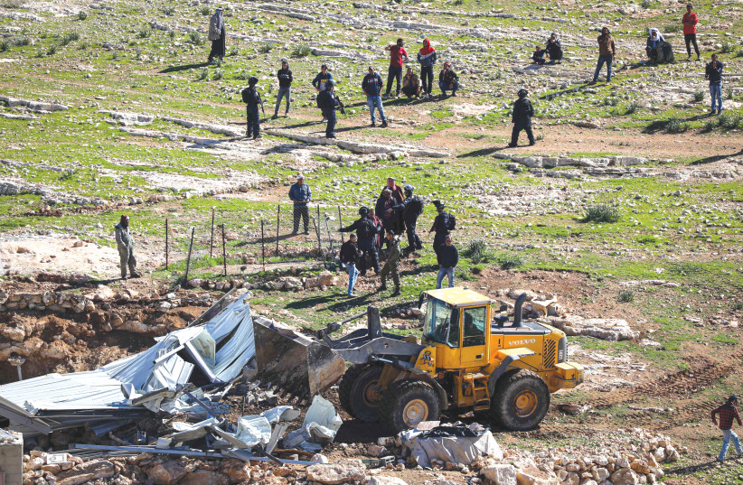 A BULLDOZER is used to demolish a shed in the West Bank village of Masafer in February 2020. (photo credit: WISAM HASHLAMOUN/FLASH90)