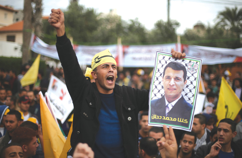 A MAN holds a poster of former Gaza Fatah leader Mohammed Dahlan during a protest against PA President Mahmoud Abbas in Gaza City in 2014. (photo credit: REUTERS)