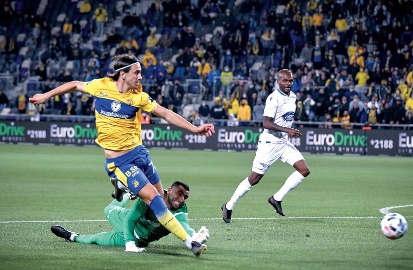 MACCABI TEL AVIV forward Aleksandar Pesic scores his team's first goal past Maccabi Petah Tikva 'keeper Arik Yanko in the yellow-and-blue's 3-1 victory at Bloomfield. (photo credit: ARIEL SHALOM)