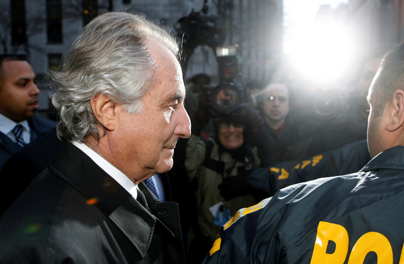 Disgraced financier Bernard Madoff is escorted by police and photographed by the media as he departs US Federal Court after a hearing in New York, January 5, 2009. (photo credit: LUCAS JACKSON/REUTERS)
