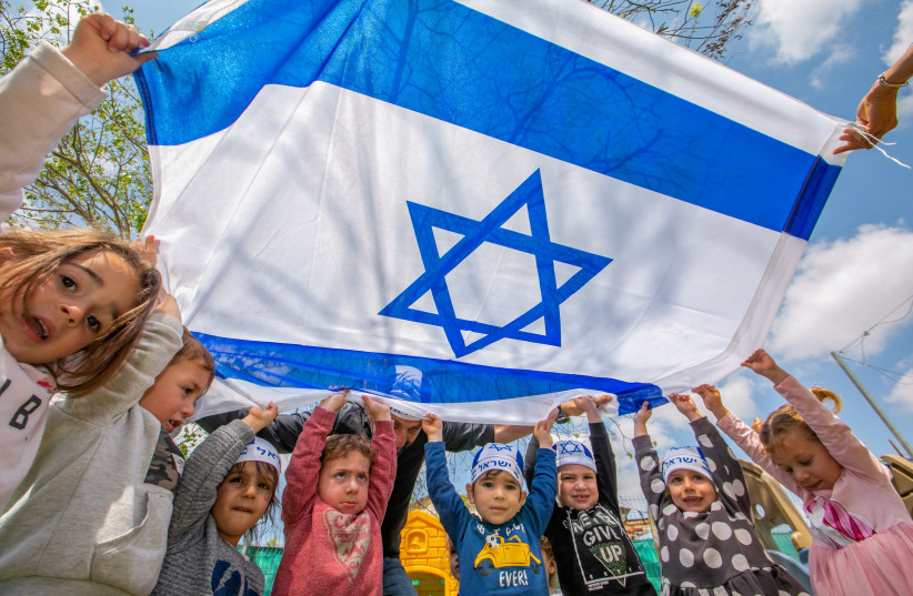 Israeli children's hold Israeli flags ahed of Israel 73rd Independence day, at a kindergarten in Moshav Yashresh, April 13, 2021.  (credit: YOSSI ALONI/FLASH90)