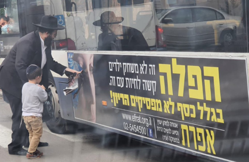 A father shows his son how to pull a woman's face off an anti-abortion organization's bus ad (photo credit: ISRAEL COHEN ON TWITTER)