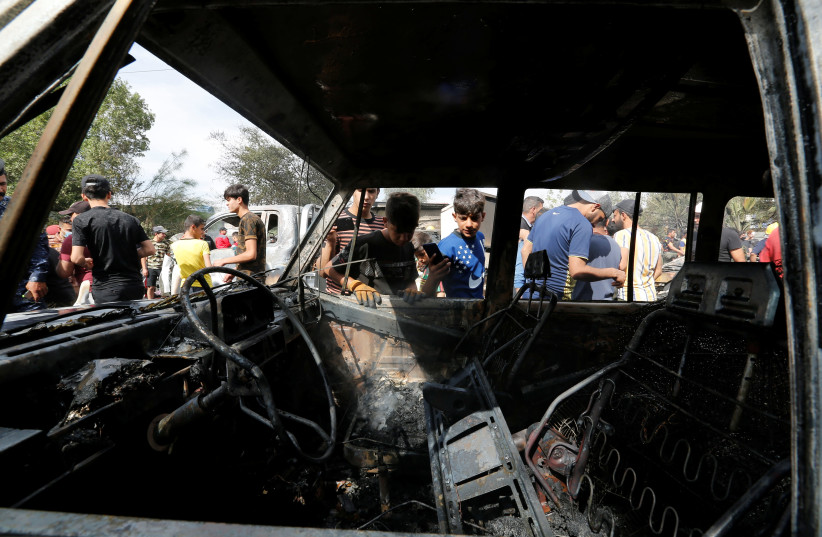 People inspect the site of a car bomb attack in Sadr City district of Baghdad, Iraq April 15, 2021. (photo credit: WISSAM AL-OKAILI/REUTERS)