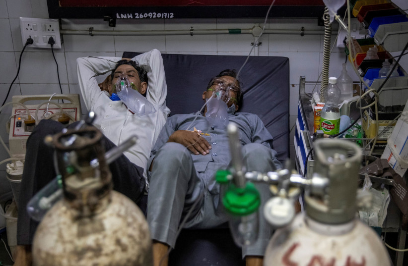 Patients suffering from the coronavirus disease (COVID-19) get treatment at the casualty ward in Lok Nayak Jai Prakash (LNJP) hospital, amidst the spread of the disease in New Delhi, India April 15, 2021.  (photo credit: REUTERS/DANISH SIDDIQUI)